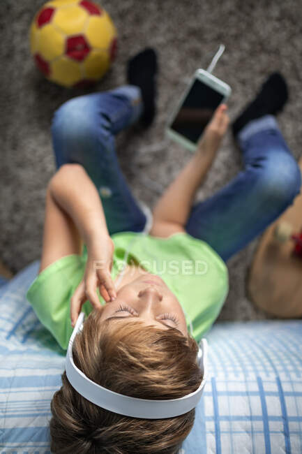 Little boy with headphones listening to music and chatting with friends in social network while sitting near skateboard in bedroom — Stock Photo