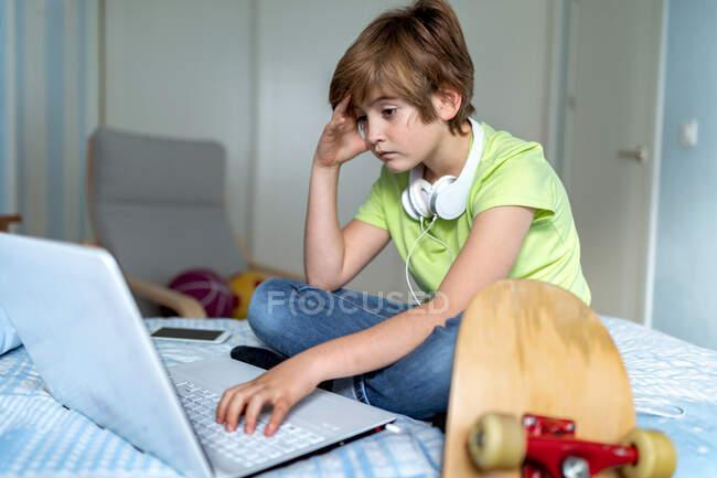Menino deprimido com fones de ouvido no pescoço sentado na cama e usando laptop enquanto passa o tempo durante o auto-isolamento por causa do coronavírus em casa — Fotografia de Stock
