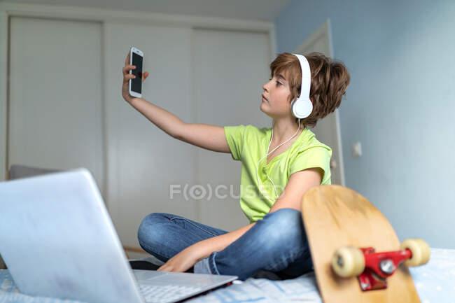 Allegro scolaro in abito casual e cuffie scattare foto con smartphone p a casa — Foto stock