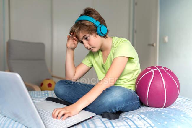 Schoolboy serio in abito casual e cuffie che giocano al videogioco sul computer portatile a casa — Foto stock