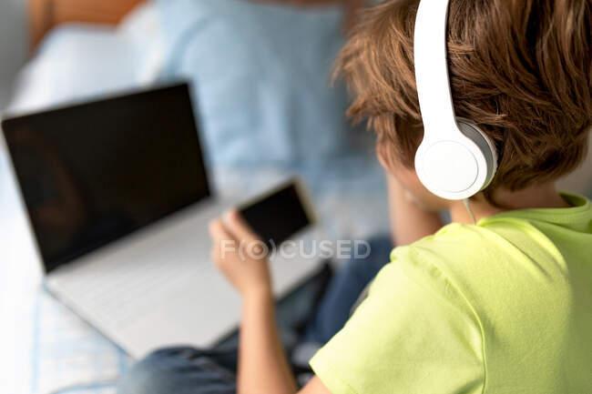 Vista posteriore dello scolaro in abito casual e cuffie che giocano a videogiochi su smartphone a casa — Foto stock