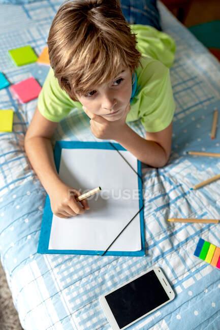 Dall'alto di bambino premuroso in abbigliamento casual sdraiato sul letto con smartphone posizionato nelle vicinanze e disegno su foglio di carta con matite colorate mentre trascorreva del tempo a casa — Foto stock