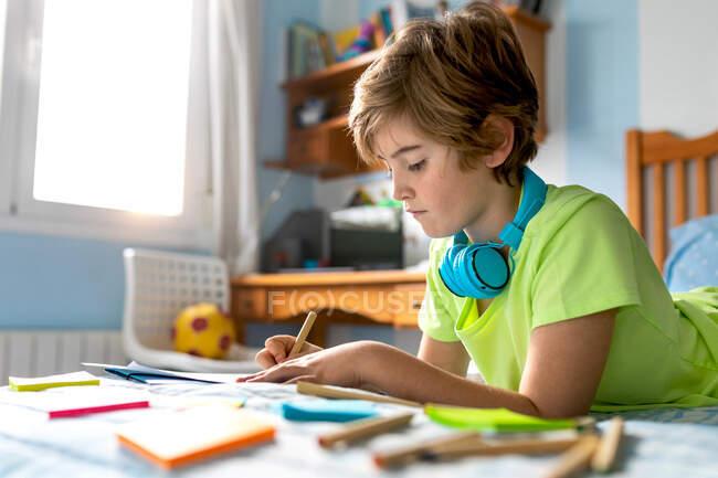 Studioso premuroso in abbigliamento casual e cuffie wireless godendo di musica e disegno con matite mentre trascorre il tempo libero in camera da letto — Foto stock