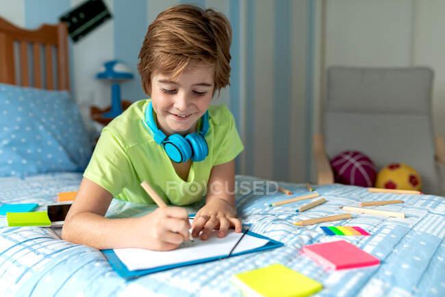 Vista laterale di scolaro positivo in abbigliamento casual e cuffie wireless godendo di musica e disegno con matite mentre trascorre il tempo libero in camera da letto — Foto stock