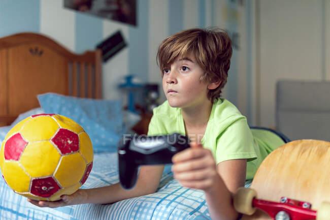 Серйозний маленький хлопчик проводить час удома і грає у відеоігри, лежачи на ліжку з м'ячем і скейтбордом. — стокове фото
