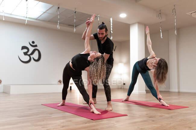 Сбалансированные спокойные женщины и мужчина учитель помогает корректировать позу на расширенный угол позы на йоге класса — стоковое фото