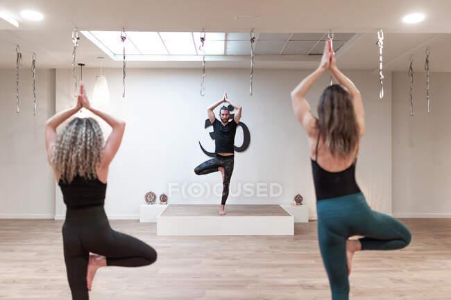 Обратный вид сбалансированного спокойствия женщин, наблюдающих за мужским учителем, стоящим на занятиях по йоге — стоковое фото