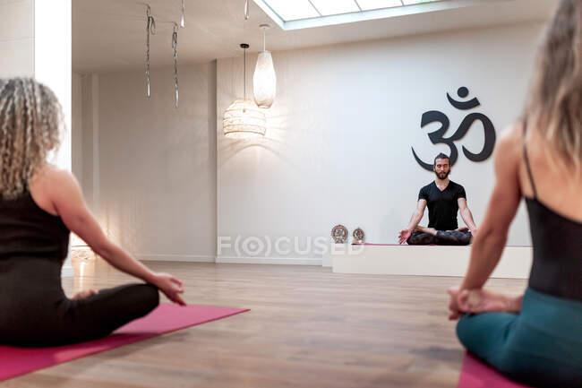 Задний вид сбалансированного спокойствия женщины и мужчина сидя на позу лотоса с мудрой сосредоточены после занятий йогой — стоковое фото