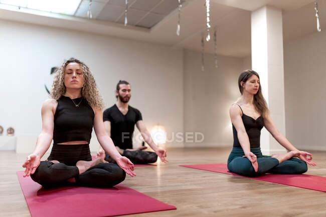 Спокойный релаксант женщины и мужчина с закрытыми глазами сидя на позу лотоса с мудрой руки сосредоточены после занятий йогой — стоковое фото