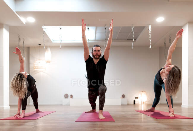 Balanced calm women and man concentrated on stretching and raising hands up in warrior one posture and extended side angle pose on yoga class — Stock Photo