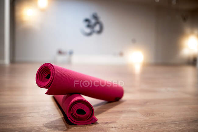 Yoga rolled pink mats placed on floor in spacious brightly illuminated studio — Stock Photo