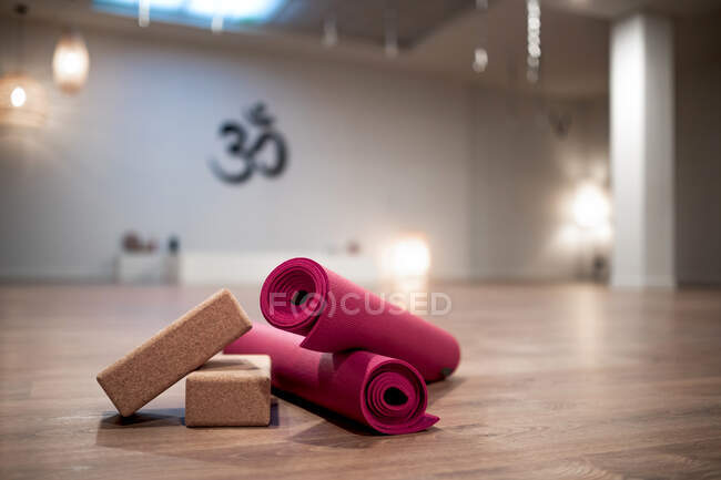 Yoga blocks and rolled pink mats placed on floor in spacious brightly illuminated studio — Stock Photo