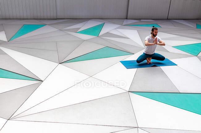 Бородатый парень в спортивной одежде, практикующий приседание на пальцах ног с жестом мудры молитвы в просторной комнате с геометрической стеной и полом — стоковое фото