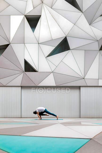 Vista lateral do homem adulto em sportswear fazendo prancha pose joelho a cotovelo exercício ao fazer ioga contra a parede geométrica em quarto espaçoso — Fotografia de Stock