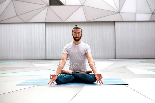 Бородатый парень в спортивной одежде сидит в позе лотоса и медитирует с закрытыми глазами и жестом мудры в просторной комнате с геометрической стеной и полом — стоковое фото