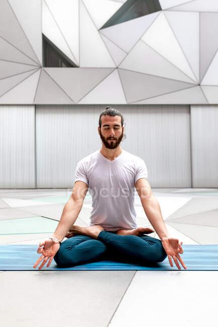 Бородатый парень в спортивной одежде сидит в позе Лотоса и медитирует с закрытыми глазами в просторной комнате с геометрической стеной и полом — стоковое фото