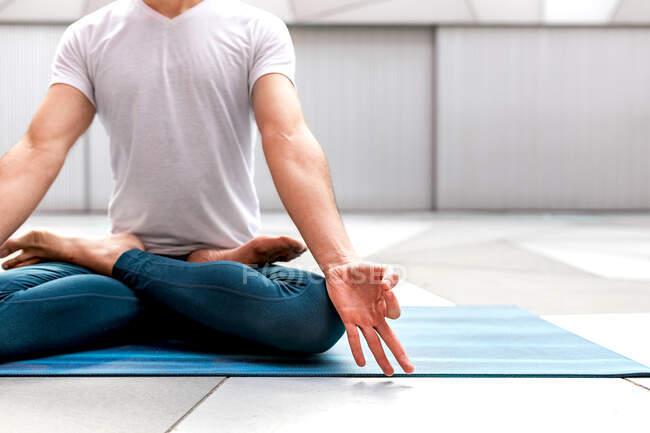 Обрезанный неузнаваемый мужчина в спортивной одежде, сидящий в позе Лотоса и медитирующий с закрытыми глазами и жестом мудры в просторной комнате с геометрической стеной и полом — стоковое фото