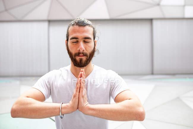 Homme barbu adulte en tenue de sport assis à méditer les yeux fermés et les mains jointes pendant l'entraînement de yoga dans la salle géométrique — Photo de stock
