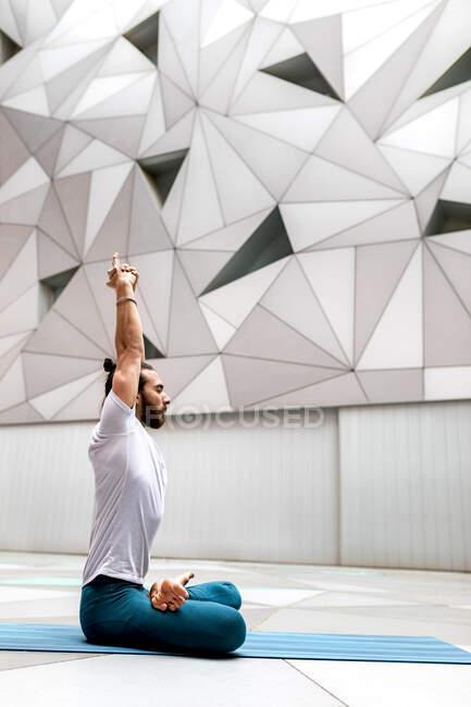 Взрослый бородатый мужчина в костюме, сидящий, скрещенный, с закрытыми глазами и поднимающий руки во время занятий йогой в геометрической комнате — стоковое фото