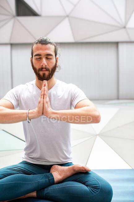 Взрослый бородатый мужчина в костюме, сидящий, скрещенный, с закрытыми глазами и согнутыми руками, во время занятий йогой в геометрической комнате — стоковое фото
