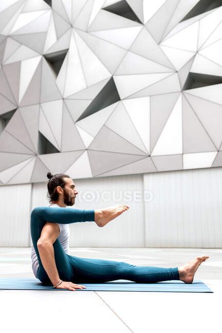 Side view of adult bearded man keeping leg on shoulder while doing stretching yoga exercise against wall with geometric ornament — Stock Photo