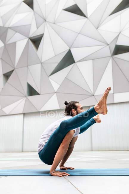 Seitenansicht eines erwachsenen bärtigen Mannes, der Yoga-Glühwürmchen gegen Wand mit geometrischem Ornament posiert — Stockfoto