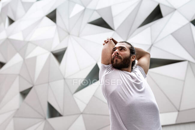 From below bearded guy in white t shirt looking away and doing stretching exercise for arms while doing yoga training against ornamental geometric wall — Stock Photo