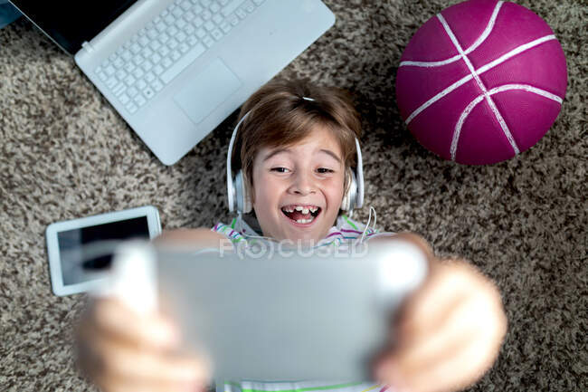 From above of cheerful little boy in headphones lying on floor near gadgets and ball and playing video game on tablet while spending time at home — Stock Photo