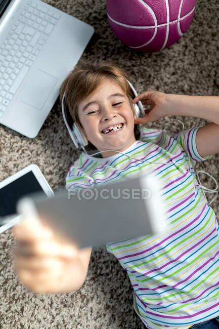 Dall'alto allegro ragazzino in camicia casual che ascolta musica con le cuffie mentre giace sul tappeto vicino a gadget e skateboard in camera da letto — Foto stock