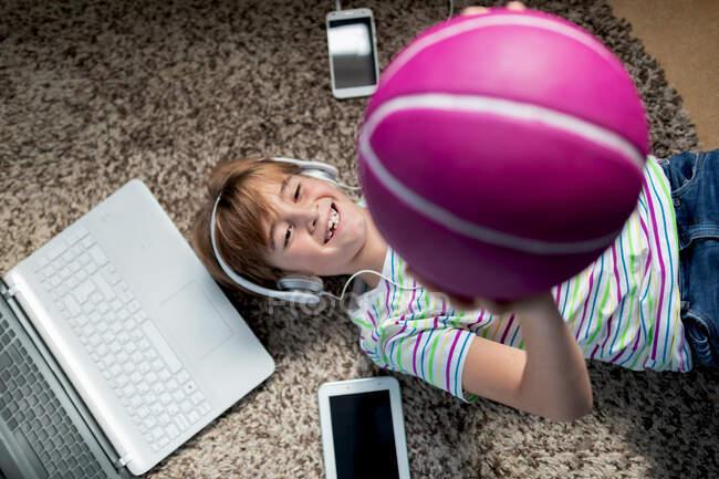 Сверху веселый мальчик в повседневной одежде слушает музыку с наушниками и смартфоном и бросает мяч, лежа на ковре в комнате — стоковое фото