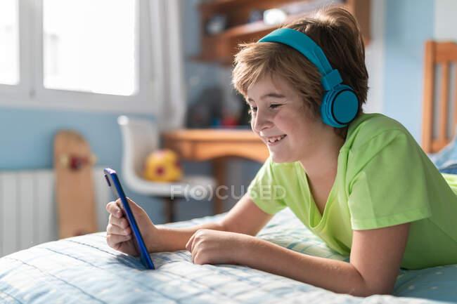 Positivo ragazzo preadolescente in abbigliamento casual con cuffie sdraiato sul letto e guardare film su smartphone mentre si riposa a casa — Foto stock