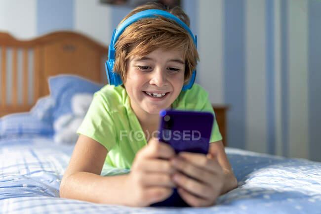 Позитивный подросток в повседневной одежде с наушниками, лежащими на кровати и смотрящими кино на смартфоне, отдыхая дома — стоковое фото