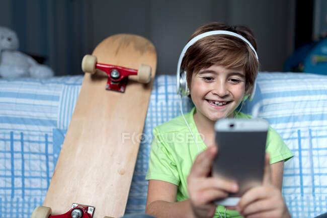 Ragazzino ridente con le cuffie che ascolta musica e chatta con gli amici sui social network mentre siede vicino allo skateboard in camera da letto — Foto stock
