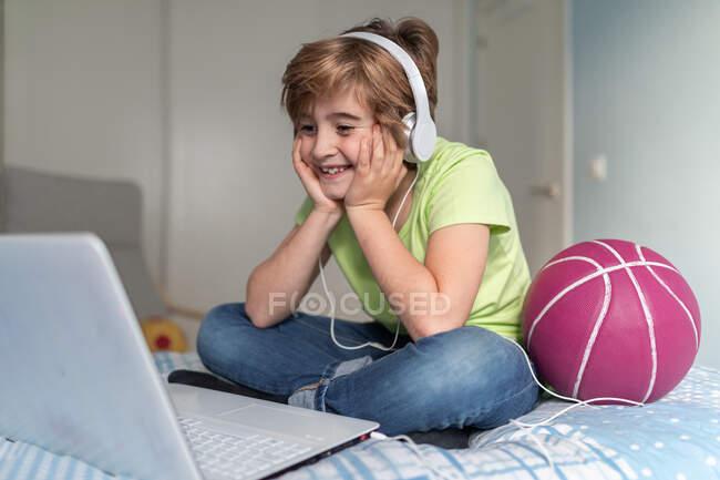 Веселый школьник в повседневной одежде и наушниках смотрит что-то на ноутбуке дома — стоковое фото