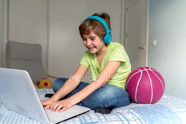 Cheerful schoolboy in casual outfit and headphones playing video game on laptop at home — Stock Photo