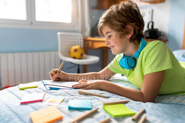 Vista laterale di scolaro positivo in abbigliamento casual e cuffie wireless disegno con matite mentre trascorre il tempo libero in camera da letto — Foto stock