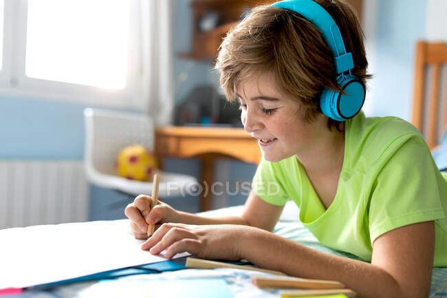 Side view of positive schoolboy in casual wear and wireless headphones drawing with pencils while spending free time in bedroom — Stock Photo