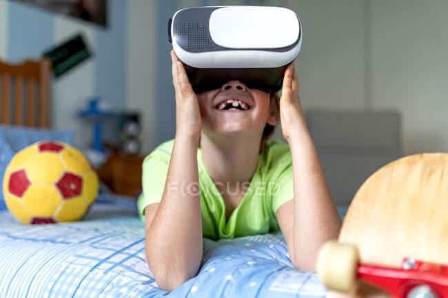 Allegro bambino con occhiali VR che si gode la realtà virtuale sdraiato sul letto vicino a palla e skateboard durante il fine settimana a casa — Foto stock