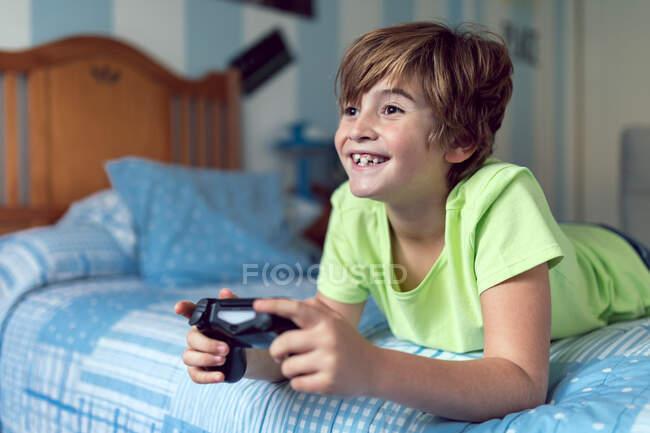 Allegro ragazzino trascorrere del tempo a casa e giocare al video gioco mentre sdraiato sul letto — Foto stock