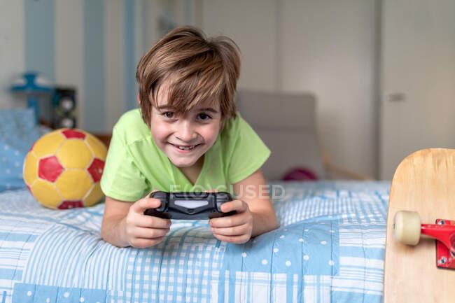 Fröhlicher kleiner Junge, der Zeit zu Hause verbringt und Videospiel spielt, während er mit Ball und Skateboard in der Nähe im Bett liegt — Stockfoto