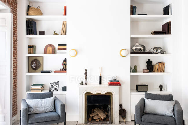 Comodi sedili grigi situati vicino al camino e alla libreria in un accogliente soggiorno in un elegante appartamento — Foto stock