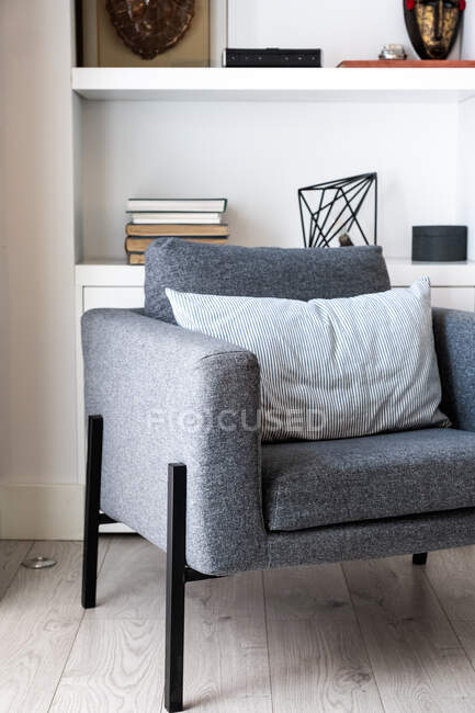 Comfortable grey seats located near fireplace and bookshelf in cozy living room in stylish apartment — Stock Photo