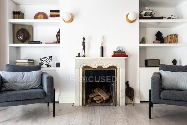 Cómodos asientos grises ubicados cerca de la chimenea y estantería en la acogedora sala de estar en un elegante apartamento - foto de stock