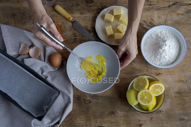 Vue du dessus de la récolte femme anonyme fouettant des œufs dans un bol noir sur une table en bois avec du citron, de la farine, du beurre et des bâtonnets de cannelle ingrédients pour gâteau — Photo de stock
