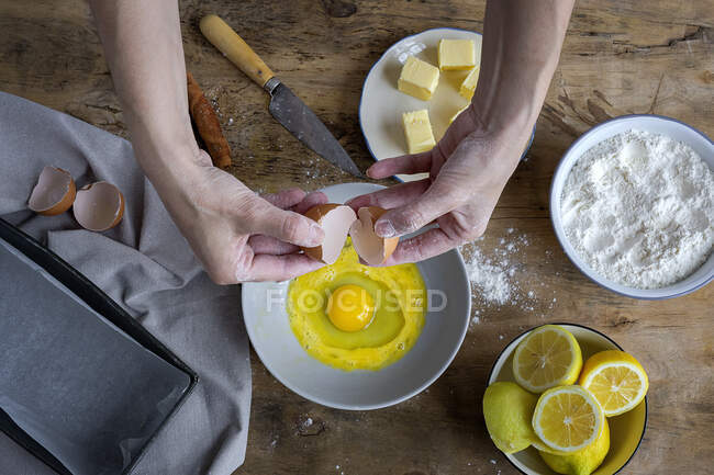 From above top view unrecognizable female breaking fresh chicken egg into bowl while cooking pastry in a wooden table with fresh ingredients — Stock Photo