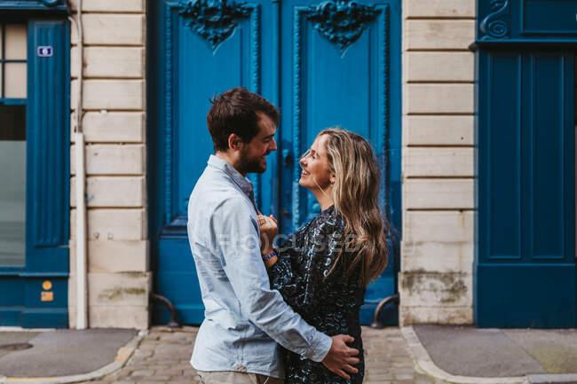 Вид сбоку счастливой молодой пары в повседневной одежде, обнимающей друг друга, смотрящей друг на друга, стоя перед старым каменным зданием с голубыми дверями на городской улице — стоковое фото