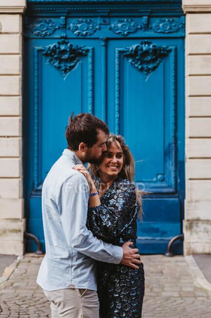 Vue latérale du jeune couple heureux en vêtements décontractés étreignant et embrassant tout en se tenant contre un bâtiment en pierre vieilli avec des portes bleues sur la rue de la ville — Photo de stock