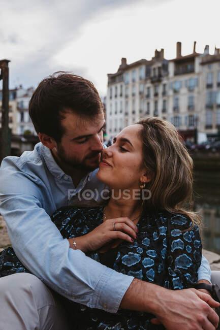 Jeune couple positif en vêtements décontractés profitant d'une date romantique tout en étant assis ensemble sur la frontière de pierre dans la ville avec de vieux bâtiments en arrière-plan — Photo de stock