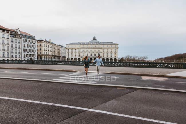 Счастливая молодая романтическая пара в стильной одежде, смеявшись и держась за руки, пересекая мост с историческими зданиями на заднем плане во время экскурсии по городу Байонна во Франции — стоковое фото