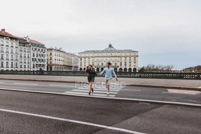 Glückliches junges romantisches Paar in stylischer Kleidung, lachend und Händchenhaltend, während es die Brücke mit historischen Gebäuden im Hintergrund während einer Stadtrundfahrt in Bayonne in Frankreich überquert — Stockfoto